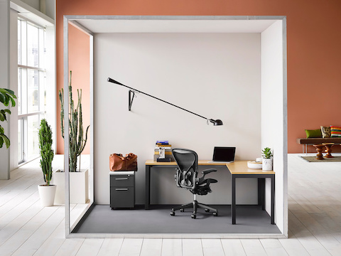 A semi-enclosed touchdown space containing an L-shaped Layout Studio surface, black Aeron office chair, and Tu storage pedestal.