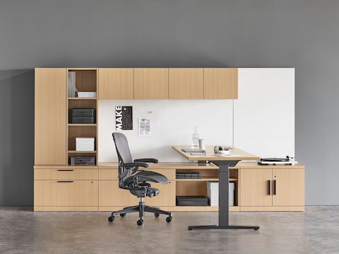 A Canvas Private Office with light wood storage, height adjustable desk, black Aeron chair, and light grey Striad lounge chair.