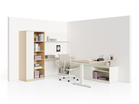 A Renew Sit-to-Stand Table placed perpendicular to a Canvas Private Office credenza, with a storage tower and shelves along the back wall.