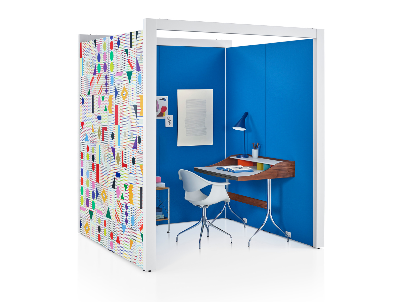 A three-sided Overlay space with blue tackable fabric interiors and colorful geometric pattern on the exterior wall with a chair and desk inside.