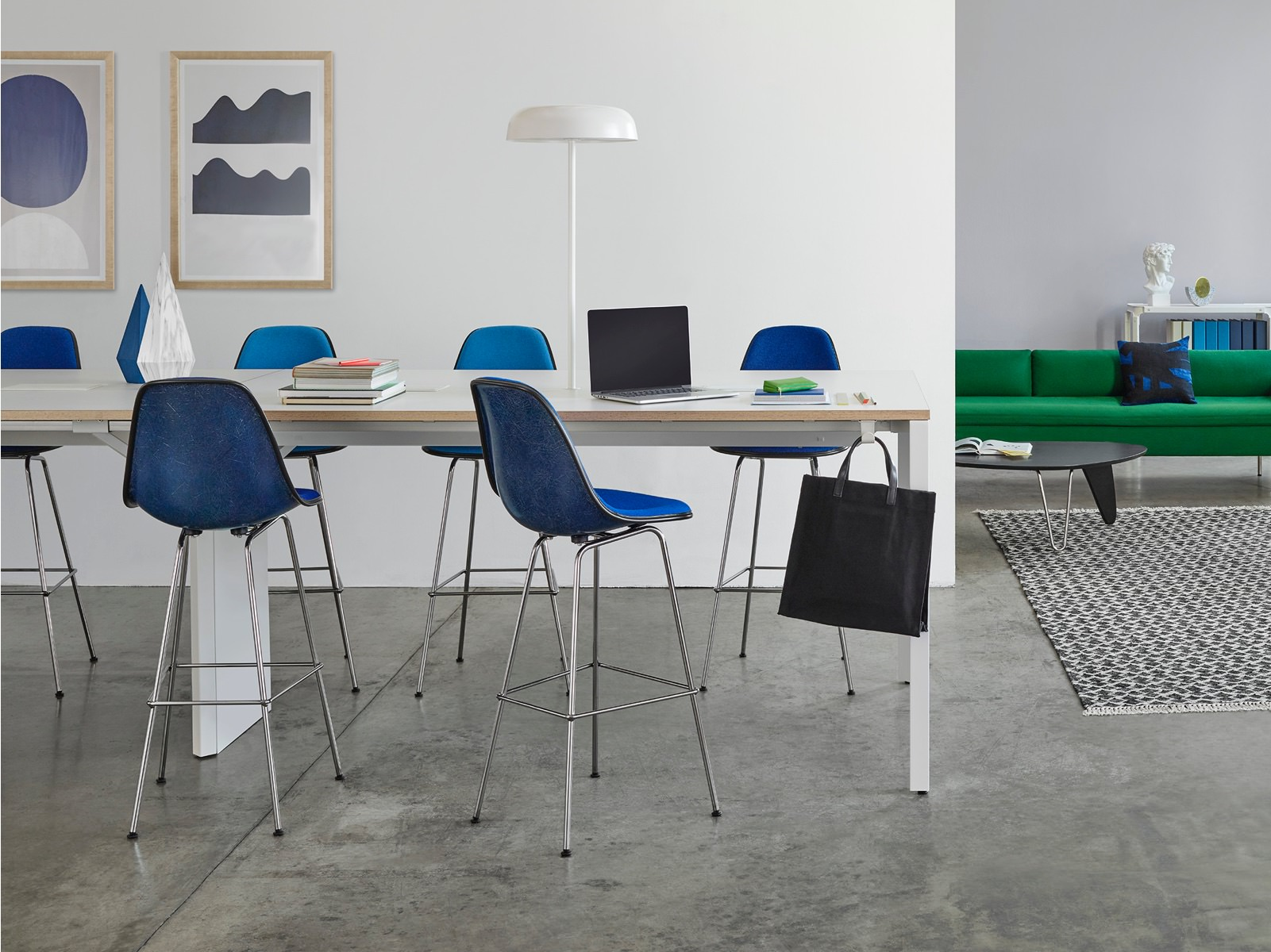 An interaction area with a Layout Studio meeting table offers a mix of seating, including a green Bolster Sofa and blue stools and side chairs.