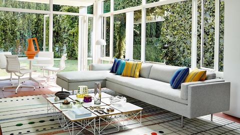 A bright, light living room with a Bolster sofa in white fabric next to a selection of Eames Low Wire Tables with white laminate set as coffee tables.