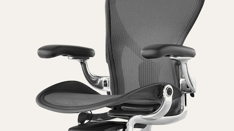 An Aeron chair with black frame and pellicle, chrome metal accents, and lumbar support.