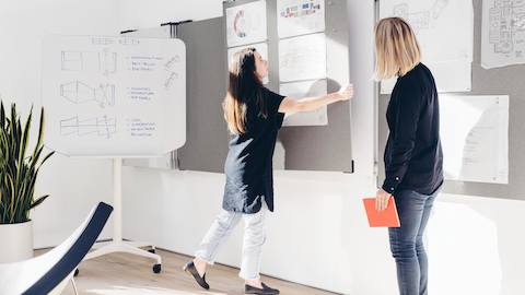 Two women examine sketches on whiteboards and inspiration pieces tacked to tack boards in a collaborative space.