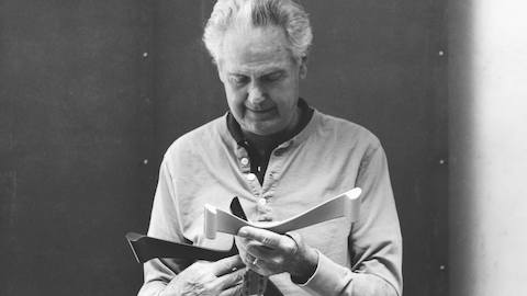 Black and white photograph of Don Chadwick, co-designer of the Aeron ergonomic desk chair, examining chair parts.