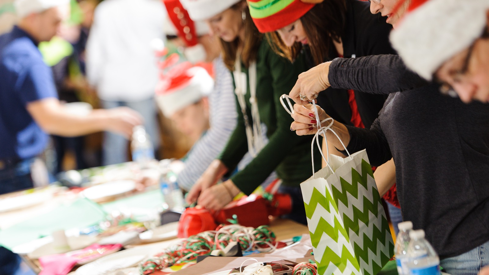 People wearing festive holiday attire assemble brightly colored gift bags during a We Care event.