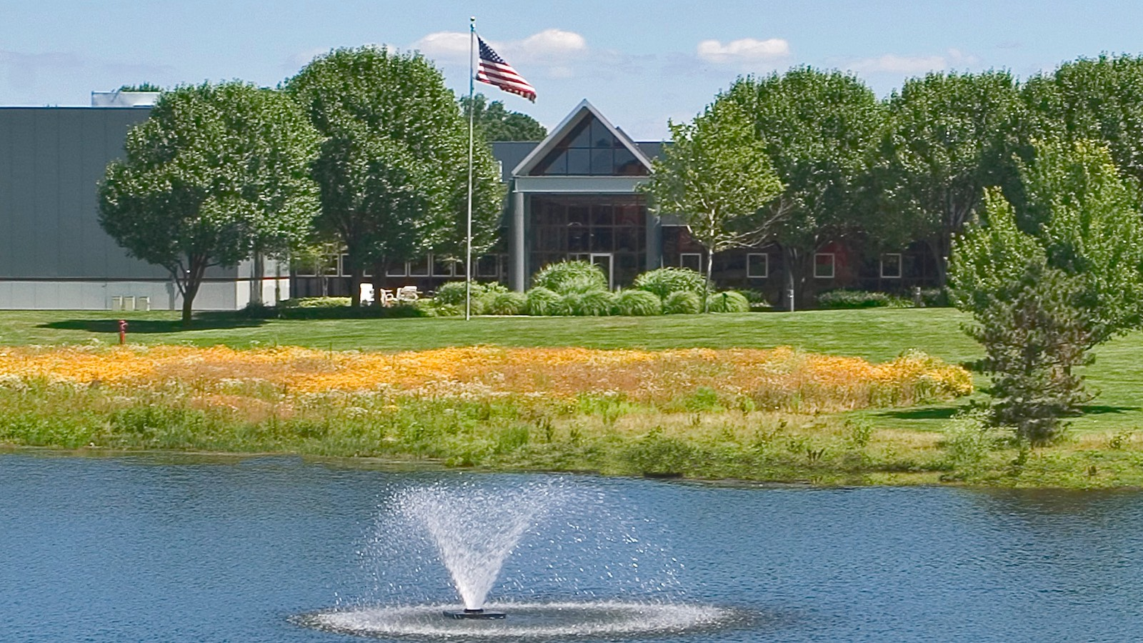 An outdoor photograph during a sunny day of a Herman Miller facility surrounded by lush landscaping, with a pond and fountain nearby.