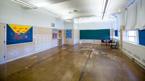 An interior photograph of an empty classroom without desks or chairs.