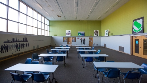 A classroom with blue chairs and tables with white tops, with illustrations on the walls and large, high windows.