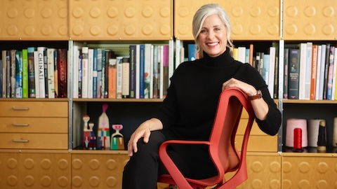 Andi Owen, President and CEO of Herman Miller, sits in a red Cosm Chair.