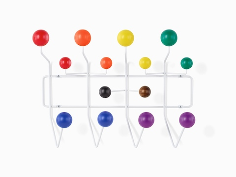 An Eames Pride Hang-It-All, showing a white wire frame and rainbow-coloured knobs
