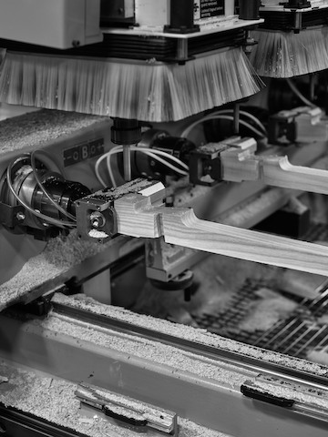 A black and white photograph of automatic milling machines carving wooden furniture parts.