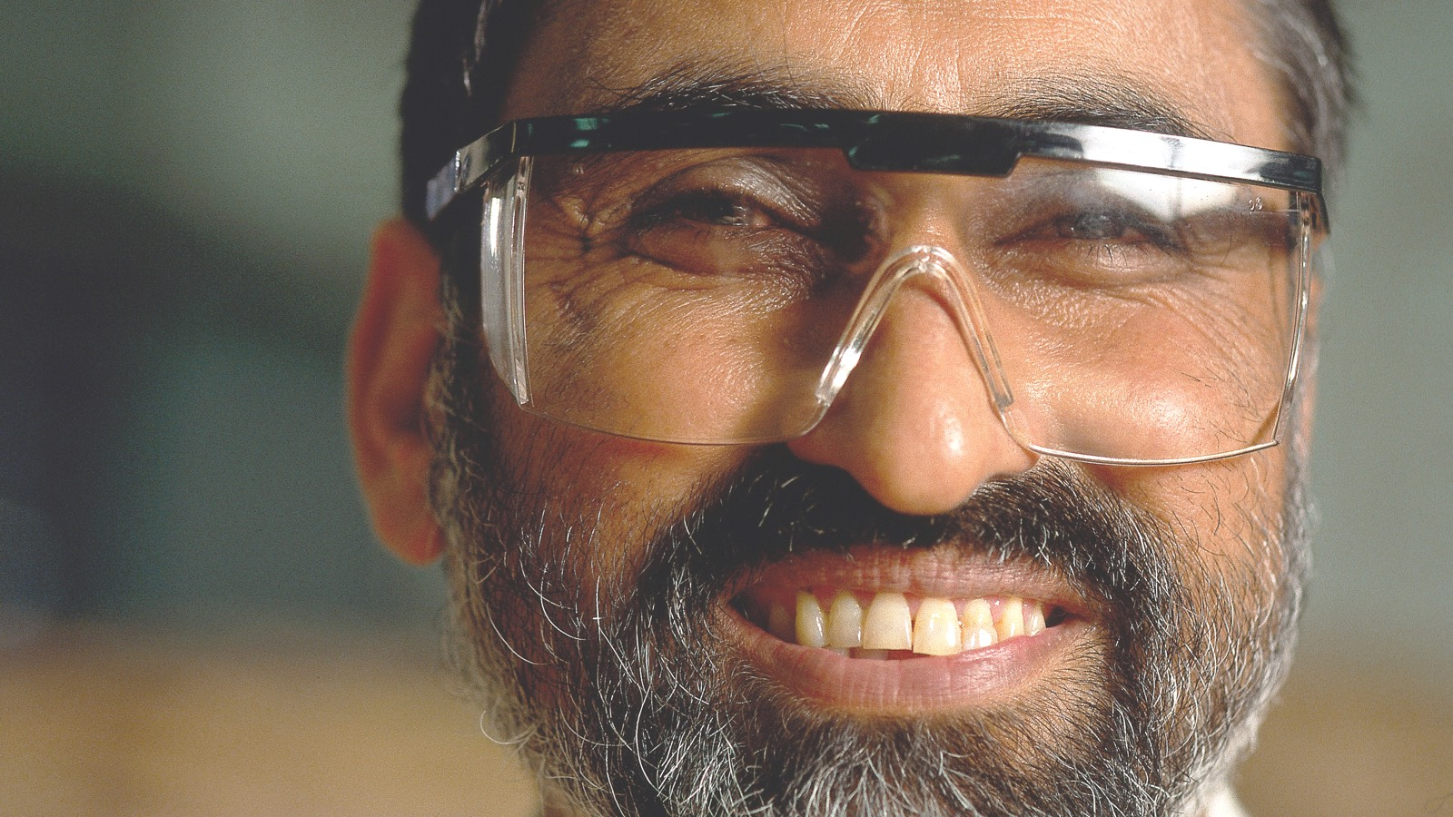 A bearded man wearing safety glasses stands in a factory and smiles.