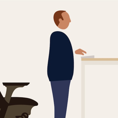 An illustration of a man standing between an office chair and a standing-height work surface.