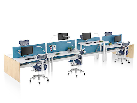 A Renew Link standing desk system with eight work surfaces, blue fabric screens, and blue and white Mirra 2 office chairs. Two of the work surfaces are raised to standing height.