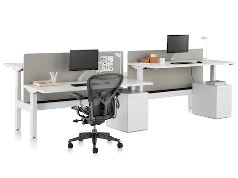 A Nevi Link standing desk system with four work surfaces, gray fabric screens, and a black Aeron office chair. One of the work surfaces is raised to standing height.