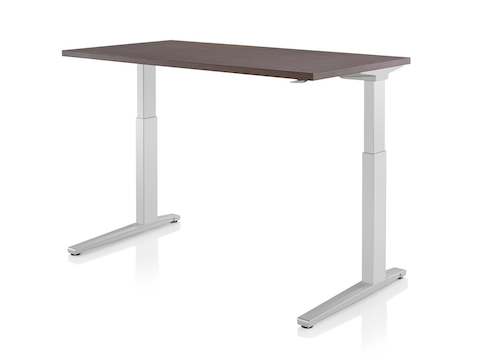 A Renew standing desk with light gray legs and dark wood work surface raised to standing height.