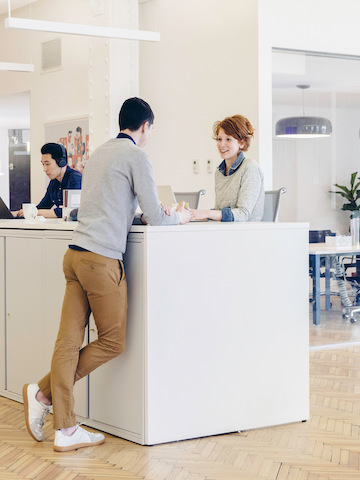 Two people talking at a standing-height work surface in the middle of an office setting.
