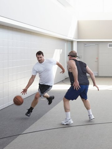 Two men play basketball indoors. One dribbles the ball across the three point line while the other tries to defend.