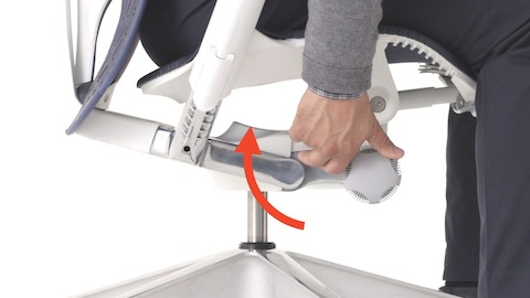 A low view of a Mirra 2 chair with white frame as a person sits in it and demonstrates adjusting the tilt tension control knob.