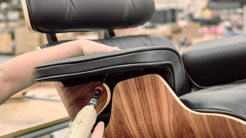 A worker attaches a black leather armpad to an Eames Lounge Chair with dark walnut shell.