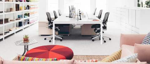 A view down the center of a bench workstation in an open office with black Aeron & Contact Information - Herman Miller