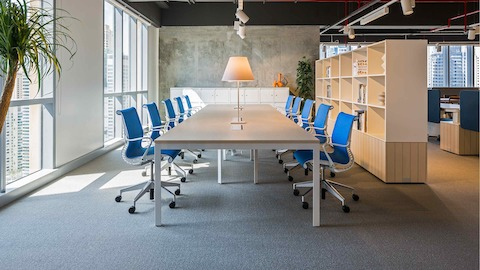 A conference setting in the Dubai showroom featuring ten Setu Chairs in blue fabric surrounding a conference table.