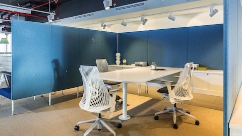 A meeting setting in the Dubai showroom, featuring Sail Chairs around a white meeting table.