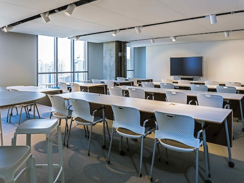 A classroom setting in the Dubai showroom, featuring Caper Chairs alongside rows of training tables.