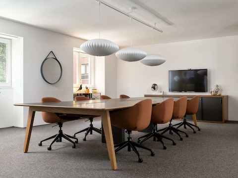 Five grey Aeron Chairs surround a work table in the Milan showroom.