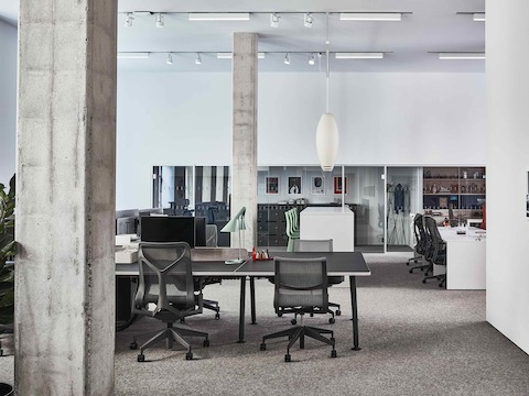 A workspace within the Paris showroom, featuring Setu and Cosm chairs around a black Memo desk.