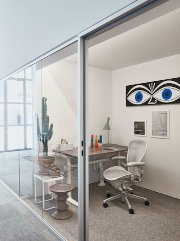A private, glass walled office within the Paris showroom, with an Aeron chair and Atlas desk.