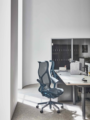 Workspace within the Paris showroom, with blue high back Cosm chairs around an Atlas desk.