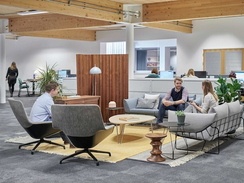 People meet in a casual work setting featuring Striad Chairs and Wireframe Sofa Group.