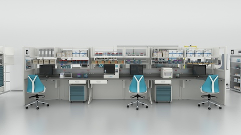 A pair of teal and white Sayl Chairs from Herman Miller sitting at a laboratory workstation that will be used to process COVID-19 tests.