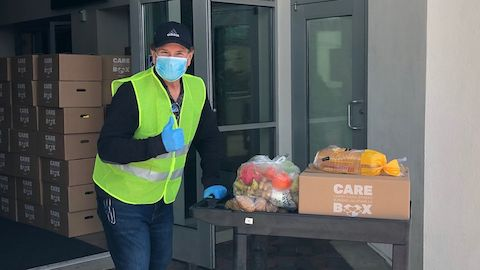 A Herman Miller employee wearing a face mask and green safety vest giving a thumbs-up while rolling a cart full of supplies.