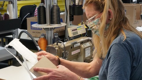 A Herman Miller employee sewing a face mask in a manufacturing space.