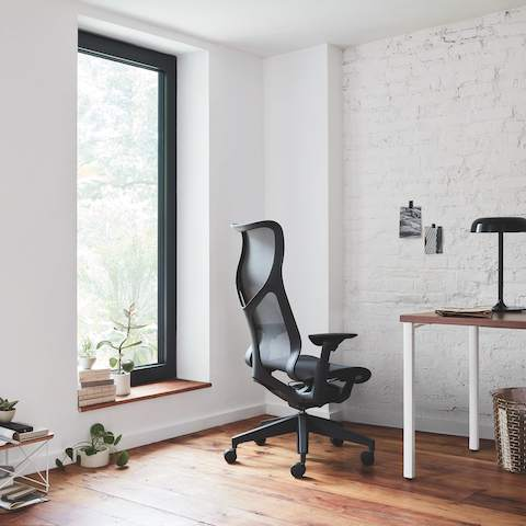 A white-walled home office with a big window, dark grey Cosm Chair, a white and brown desk, an Eames Wire Base Low Table, plants, books, and other office accessories.