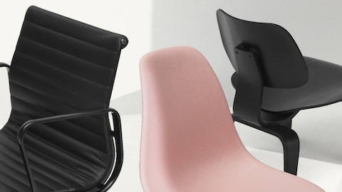 A black leather Eames Aluminum Group Chair, a pink Eames Shell Chair, and a black Eames Molded Plywood Chair grouped together.