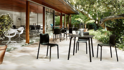 A group of black outdoor chairs around a table on a patio near a glass doorwall that looks in on a living room.