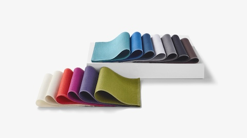 Two sets of folded, multicolor materials swatches laid out in rows with the back row elevated on a white box.