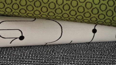 Layers of folded fabric samples, including a green patterned fabric, a black and white checked fabric, and a fabric with a lined pattern.