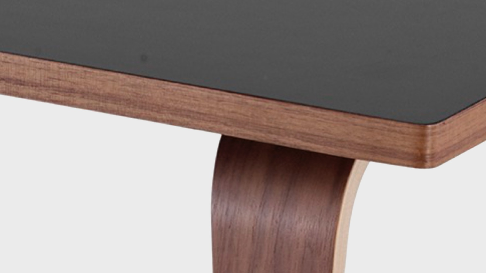 A close-up of the black laminate on top of a coffee table with walnut wood top and molded plywood legs.