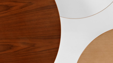 Layered tabletops in a variety of materials including walnut veneer, white laminate, and ash veneer.