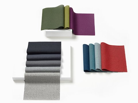 Folded gray, blue, green, and red samples of Rivet fabric.