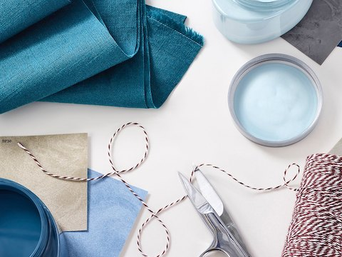 An overhead view of blue and tan fabric swatches stacked on top of each other by a folded blue fabric sample, a red and white thread, and scissors.