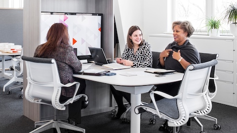 Three women sit in Setu office chairs with white frames and heathered gray upholstery around a table in a collaborative space with a large digital display.