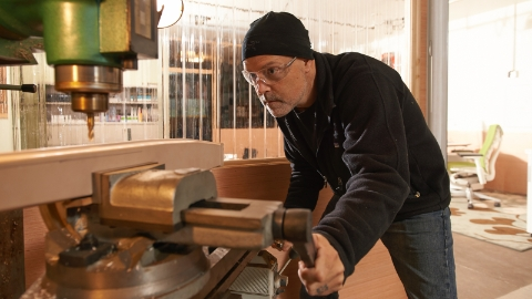 Designer Brian Alexander wearing safety glasses while working on a machine in his studio.