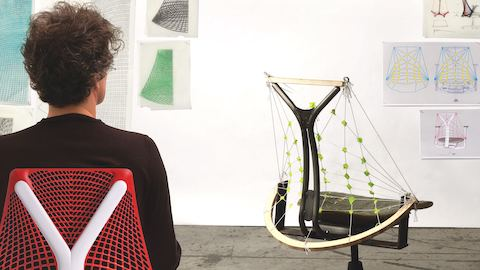 Designer Yves Béhar examines a model of the Sayl office chair.