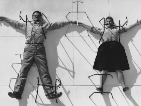 A vintage photo of Charles and Ray Eames holding hands in a playful posture.